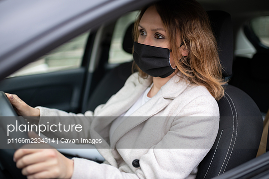 Woman in protective mask driving car - p1166m2234314 by Cavan Images