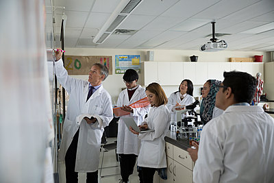 Science professor leading college students at whiteboard in laboratory - p1192m1145702 by Hero Images