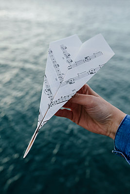 Hand at the water holding paper plane made of music sheet - p300m1166020 by Boy photography