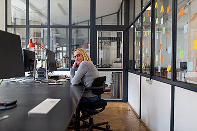 Mature businesswoman sitting at desk in office - p300m2156048 by Gustafsson