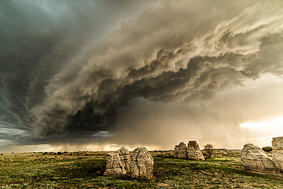 Storm clouds over rock formations in field, Lamar, Colorado, United States, North America - p429m1519567 by Jessica Moore
