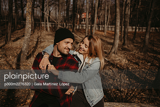 Smiling woman with arm around boyfriend sitting in forest during autumn - p300m2276320 by Gala Martínez López