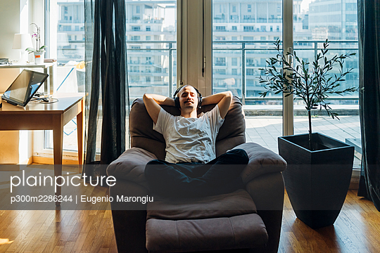 Young man with hands behind head relaxing on reclining chair at home - p300m2286244 by Eugenio Marongiu