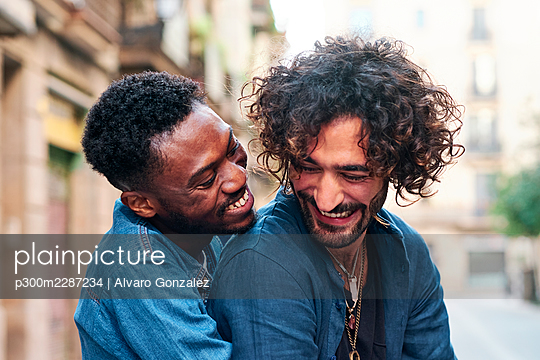 Smiling gay man embracing male friend from behind - p300m2287234 by Alvaro Gonzalez