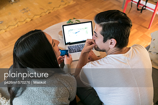 High angle view of couple shopping online through laptop on sofa at home - p426m1570276 by Maskot