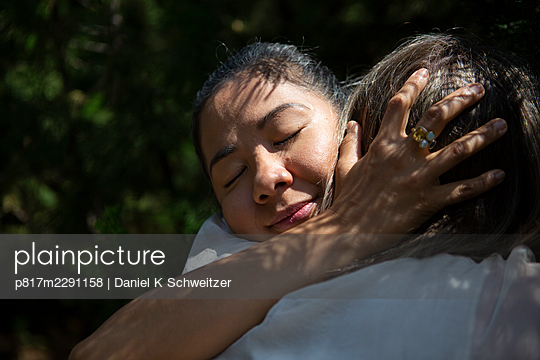 Lesbian couple embracing, portrait - p817m2291158 by Daniel K Schweitzer