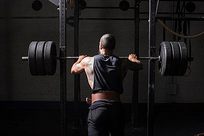 An athlete prepares to squat at a gym. - p1166m2094508 by Cavan Images