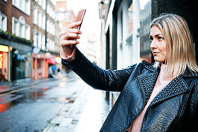 Stylish Girl Biker in Fashionable Clothes. Blond Hair Blogger Woman Making Selfie on Mobile or Smart Phone. Black leather jacket. - p1166m2227651 by Cavan Images