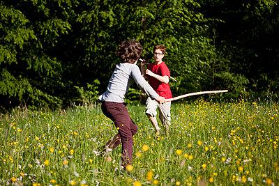 Jungen beim Stockkampf im Park - p1195m1138142 von Kathrin Brunnhofer