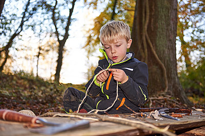 Portrait of blond little boycutting rope with knife outdoors - p300m1417028 by Jess Derboven