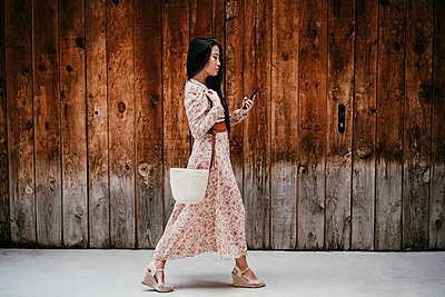 Woman using smart phone while walking by by old wooden door - p300m2274134 by Eva Blanco