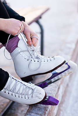 Woman putting ice skates on - p312m1107429f by Lena Granefelt