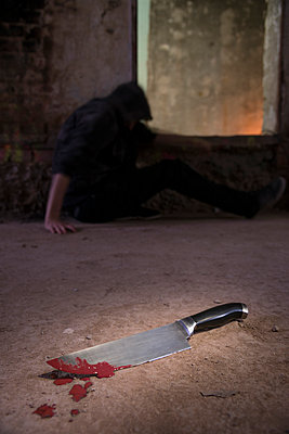 Blood-smeared knife and person in background - p335m1041629 by Andreas Körner