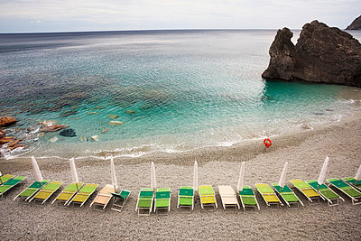 Beach chairs along the water's edge and a view of the horizon; Monterosso Al Mare, Liguria, Italy - p442m1033889 by Jenna Szerlag