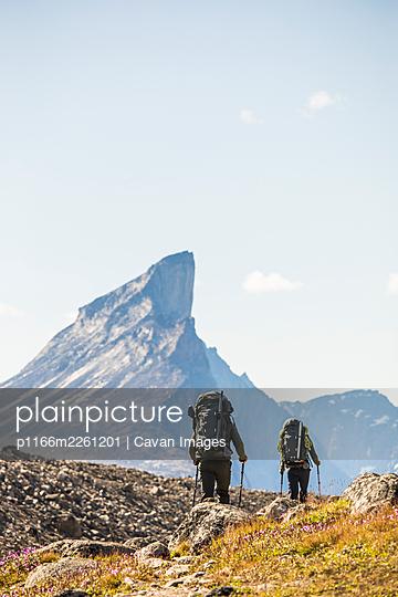 Two backpackers hike below Mt. Thor, Canada. - p1166m2261201 by Cavan Images