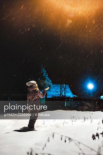 Mädchen fängt Schneeflocken mit den Händen - p1642m2222204 von V-fokuse
