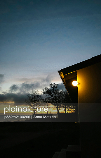 House by the sea at sunrise - p382m2100266 by Anna Matzen