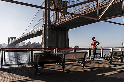 USA, New York City, man running at East River under Brooklyn Brige - p300m1191525 by Uwe Umstätter