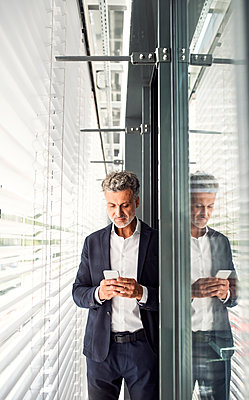 Mature businessman standing at outside sunblind holding cell phone - p300m1535997 by HalfPoint