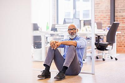 Portrait of businessman sitting on the floor of an office - p300m1567956 von Jo Kirchherr