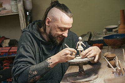 Potter working on a tiny figurine in workshop - p300m2167588 by Vasily Pindyurin