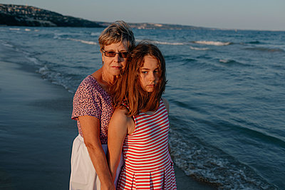 Granddaughter standing with grandmother by water at beach - p300m2267056 by Oxana Guryanova