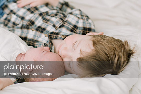 Big brother and newborn baby sister snuggling on bed - p1166m2191783 by Cavan Images