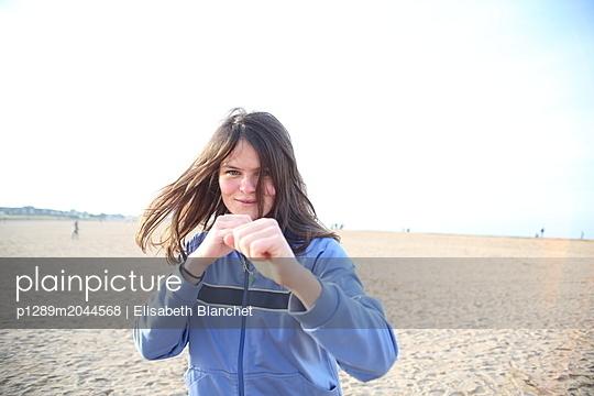 Junge Frau in Boxerpose am Strand von Riva Bella - p1289m2044568 von Elisabeth Blanchet