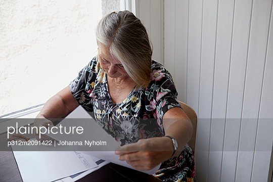 Woman reading documents - p312m2091422 by Johanna Nyholm