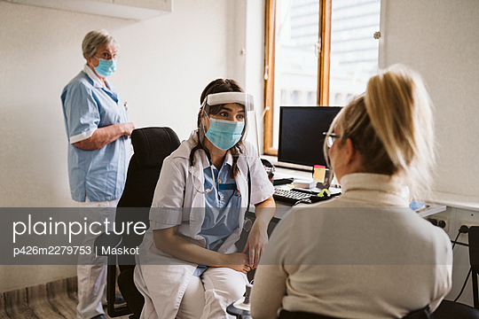 Female healthcare worker wearing mask and face shield talking patient in medical clinic - p426m2279753 by Maskot