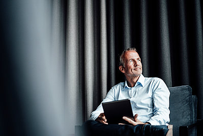 Contemplating businessman with digital tablet looking away while sitting on armchair in office cafeteria - p300m2265748 by Gustafsson