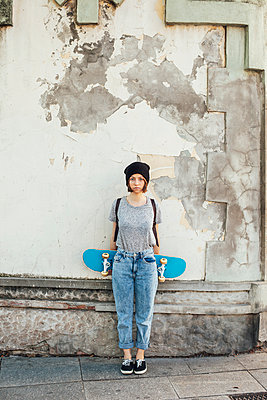 Portrait of serious looking young female skate boarder in front of facade - p300m949762f by Bonninstudio