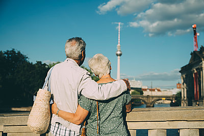 Rear view of senior couple with arm around looking at television tower from bridge in city - p426m2170299 by Maskot