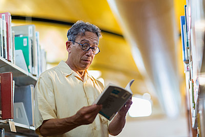 Older Caucasian man reading book in library - p555m1414238 by Marc Romanelli
