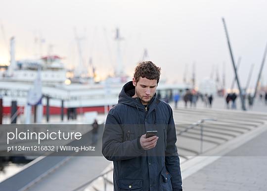 Mann am Hafen mit Smartphone - p1124m1216832 von Willing-Holtz