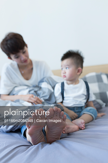 Asian mother and son sitting together on the bed at home - p1166m2084548 by Cavan Images