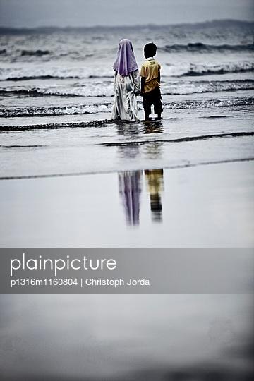 Zwei Kinder stehen am Strand im Wasser, Jakarta, Java, Indonesien - p1316m1160804 von Christoph Jorda