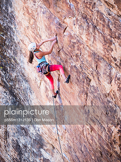 Mixed race girl rock climbing on cliff - p555m1312135 by Don Mason