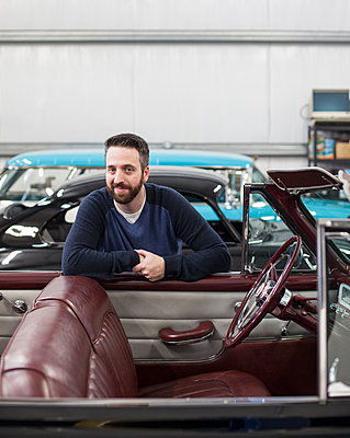 A portrait of a Caucasian male leaving on the side of his classic car convertible in a repair shop. - p1100m2002331 by Mint Images