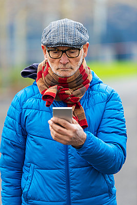Confident senior man using smart phone, while standing outdoors - p1166m2084706 by Cavan Images