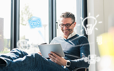 Man sitting in office, using digital tablet to remote-control his smart home - p300m1563358 by Uwe Umstätter