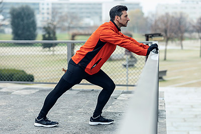 Athletic man leaning on chainlink fence while doing stretching exercise at park - p300m2275560 by Josep Suria