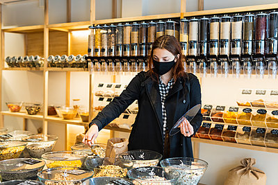 Young woman filling ingredients in paper bag during COVID-19 at store - p300m2286783 by NOVELLIMAGE