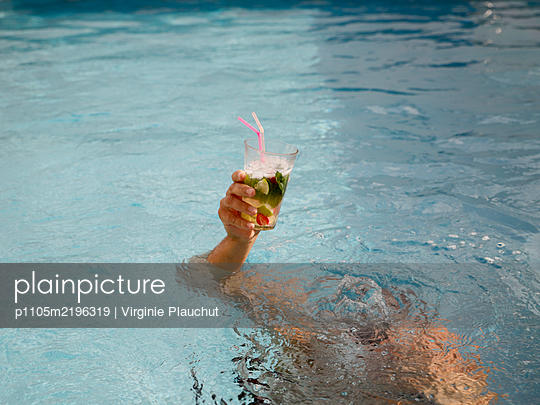 Man dives in the pool while holding drink in one hand - p1105m2196319 by Virginie Plauchut