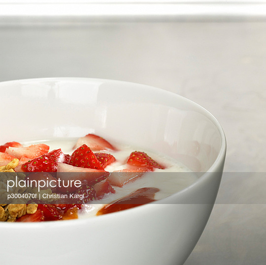 Muesli topped with yoghurt and slices of fresh strawberries, close-up