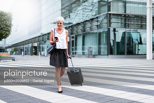 Smiling senior woman with baggage on the move looking on cell phone - p300m2028852 von Daniel Ingold