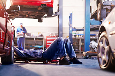 Mechanic under car in auto repair shop - p1023m1053850f by Trevor Adeline