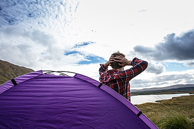 Young man on camping trip - p1082m2022024 by Daniel Allan