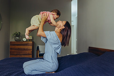 Mother lifting up her baby girl on bed - p300m2042756 by Mareen Fischinger