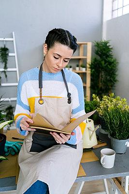 Young woman working in a gardening laboratory or plant shop - p300m2274670 von Giorgio Fochesato